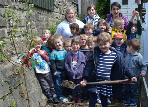 Betty Cafferty plants apple tree at Matlock Preschool Playgroup