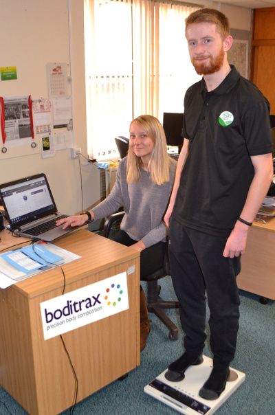 The District Council's Sports Development & Coaching Apprentice Ross Jillings on the Boditrax scales, monitored by Sports & Health Development Officer Becky Bryan